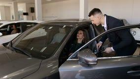 Muchacha de lujo que se sienta detrás de la rueda de un nuevo coche en la concesión de coche Venta del coche metrajes
