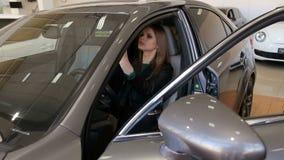 Muchacha de lujo que se sienta detr?s de la rueda de un nuevo coche en la concesi?n de coche Venta del coche almacen de video