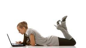 Muchacha de mentira del adolescente con la computadora portátil (aislada) Foto de archivo
