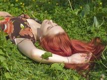 Muchacha de mentiras relaxed en la hierba fotos de archivo