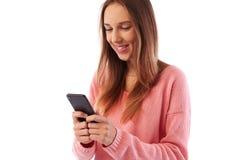 Muchacha de mirada de moda que manda un SMS en vuelta de la situación del smartphone lado-en Fotografía de archivo