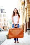Muchacha de mirada triste con equipaje en ciudad Imagen de archivo