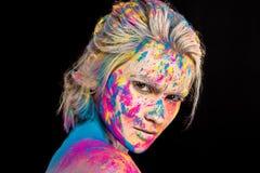 muchacha de moda atractiva que presenta en polvo colorido del holi, fotografía de archivo