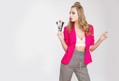 Muchacha de moda con el pelo rizado largo en los cepillos rosados de la chaqueta de una tenencia de la muchacha para el maquillaj Fotos de archivo
