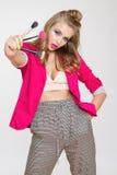 Muchacha de moda con el pelo rizado largo en los cepillos rosados de la chaqueta de una tenencia de la muchacha para el maquillaj Fotos de archivo libres de regalías