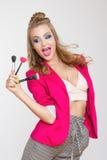 Muchacha de moda con el pelo rizado largo en los cepillos rosados de la chaqueta de una tenencia de la muchacha para el maquillaj Imagenes de archivo