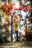 Muchacha de moda con el pelo rubio largo en la ropa elegante que se coloca en un fondo de la pintada Fotografía de archivo libre de regalías