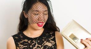 Muchacha de moda con la tenencia neta negra un bolso de oro Foto de archivo libre de regalías