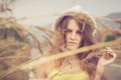 Muchacha de moda del inconformista en el sombrero que se relaja en el camino en el día t Imagen de archivo