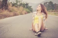 Muchacha de moda del inconformista que se relaja en el camino en el tiempo del día Fotos de archivo
