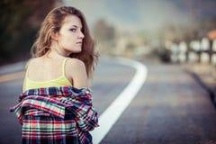 Muchacha de moda del inconformista que se relaja en el camino en el tiempo del día Foto de archivo libre de regalías