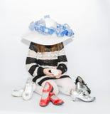 muchacha de moda del niño con la sentada elegante del sombrero y el intentar elegir, qué mejores zapatos estarán para ella hoy Fotos de archivo libres de regalías