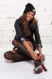 Muchacha de moda en una chaqueta negra y un sombrero con los zapatos de vestir de una sonrisa Pared de ladrillo blanca, no aislad Fotos de archivo