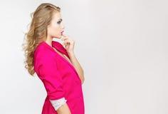 Muchacha de moda hermosa con el pelo rizado largo en una muchacha rosada de la chaqueta en el estudio en un fondo gris Foto de archivo libre de regalías