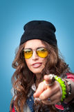 Muchacha de moda hermosa del inconformista en sombrero negro de la gorrita tejida que señala el finger en usted Fotos de archivo