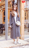 Muchacha de moda hermosa en pantalones y zapatillas de deporte grises de la capa con un bolso de moda que presenta cerca de la sa Imagenes de archivo