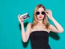 Muchacha de moda hermosa que presenta y que sostiene una cámara del vintage en vestido y gafas de sol negros en el fondo verde en Imagenes de archivo
