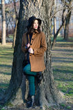 Muchacha de moda hermosa que se coloca en parque en día soleado del otoño Foto de archivo libre de regalías