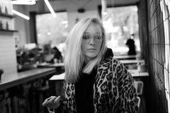 Muchacha de moda hermosa que se sienta en la barra cerca de la pared de neón, bl fotografía de archivo libre de regalías