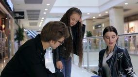 Muchacha de moda joven con los padres que miran compras en bolsos de compras almacen de video