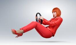 Muchacha de moda joven en coche rojo del conductor con una rueda fotos de archivo