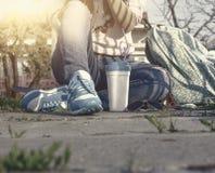 Muchacha de moda joven que se sienta en una tierra con la taza para llevar Copyspace en el asfalto Imagen de archivo libre de regalías