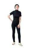 Muchacha de moda joven relajada en la camiseta negra del cuello cisne que presenta y que sonríe en la cámara Fotografía de archivo libre de regalías