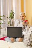 Muchacha de moda linda que se sienta en el sofá con café y el ordenador portátil fotografía de archivo libre de regalías
