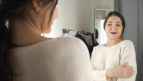 Muchacha de moda que mira en el espejo en probador almacen de video