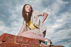 Muchacha de moda que presenta en la pared de ladrillo vieja Imagenes de archivo