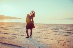 Muchacha de moda que se coloca en la playa en la puesta del sol Imágenes de archivo libres de regalías
