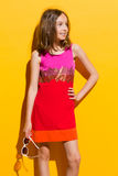 Muchacha de moda que sostiene las gafas de sol y que mira lejos Fotografía de archivo