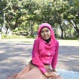Muchacha de Moeslim que se sienta en el parque fotos de archivo libres de regalías