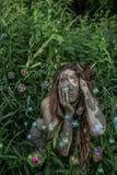 Muchacha de Muddy Amazon que oculta detrás de un arbusto en el bosque, mientras que burbujas de jabón que vuelan alrededor de ell foto de archivo