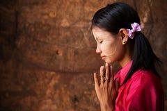 Muchacha de Myanmar en una actitud de rogación. Imagen de archivo