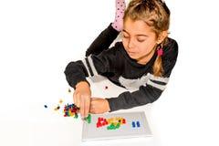 Muchacha de ocho años que juega con el juego de mesa aislado en blanco Imagenes de archivo