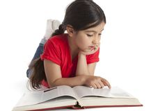 Muchacha de ocho años que lee un libro Foto de archivo