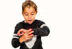 Muchacha de ocho años que mira su reloj sorprendido a que hora Fotos de archivo libres de regalías