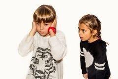 Muchacha de ocho años que está enojada y que grita en su hermana Aislador Imagen de archivo