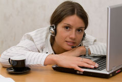 Muchacha de oficina en el escritorio con una taza y un receptor de cabeza Fotografía de archivo libre de regalías