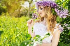Muchacha de ojos azules con la guirnalda de las flores en parque verde Foto de archivo libre de regalías