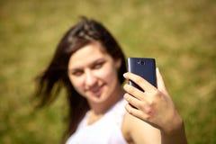 Muchacha de oriental-mirada hermosa que hace el selfie en un smartphone fotografía de archivo libre de regalías