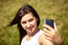 Muchacha de oriental-mirada hermosa que hace el selfie en un smartphone imagenes de archivo