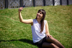 Muchacha de oriental-mirada hermosa que hace el selfie en un smartphone imágenes de archivo libres de regalías