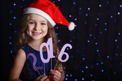 Muchacha de Papá Noel con la fecha 2016 del Año Nuevo Foto de archivo