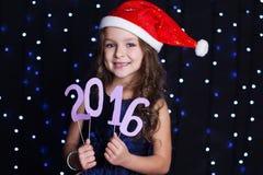 Muchacha de Papá Noel con la fecha 2016, tiempo del Año Nuevo de la Navidad Imagen de archivo
