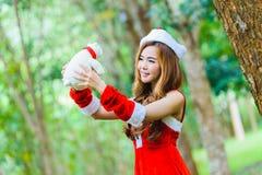 Muchacha de Papá Noel del asiático con el oso Imagen de archivo