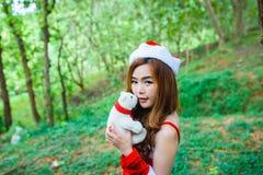 Muchacha de Papá Noel del asiático con el oso Foto de archivo