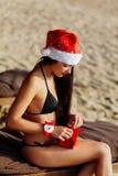 Muchacha de Papá Noel en el bikini que desempaqueta el regalo de la Navidad Imagen de archivo libre de regalías