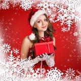Muchacha de Papá Noel en el fondo rojo con los copos de nieve Imágenes de archivo libres de regalías